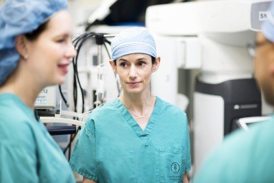 Gynecologic surgeon Kara Long Roche in green scrubs with two team members
