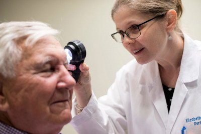 MSK dermatologist Elizabeth Quigley examines an older male patient