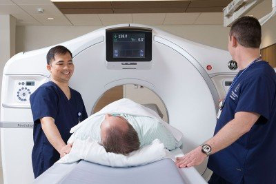 Two health care providers standing over a patient on a CT bed
