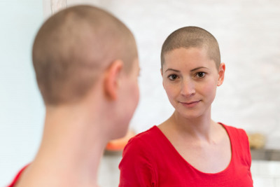 woman with shaved head in mirror