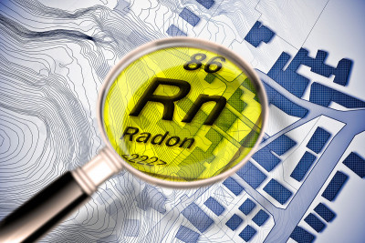 Illustration of microscope enlarging chemical symbol for radon (RN) over city map.