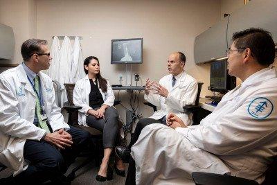 Neuroradiologist Eric Lis, clinical nurse Cynthia Correa, neurosurgeon Mark Bilsky, and radiation oncologist Josh Yamada in an office.