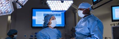 Two people in surgical scrubs stand in an operating room underneath large light panels and screens with medical information.