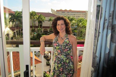 Breast cancer survivor Jill enjoying a vacation, standing on a scenic hotel balcony.