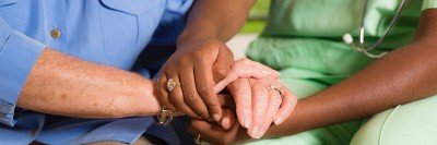 Closeup photograph of a nurse and patient holding hands