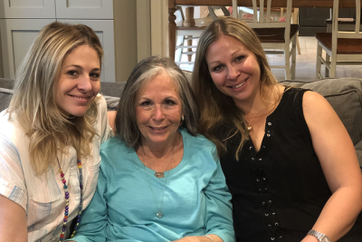 Lynne sitting on a couch with her two adult daughters.