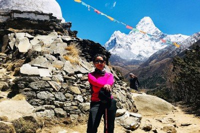 Manisha Koirala posing in hiking gear in front of Mount Everest.