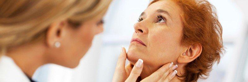 Female doctor examining woman's thyroid area (throat).