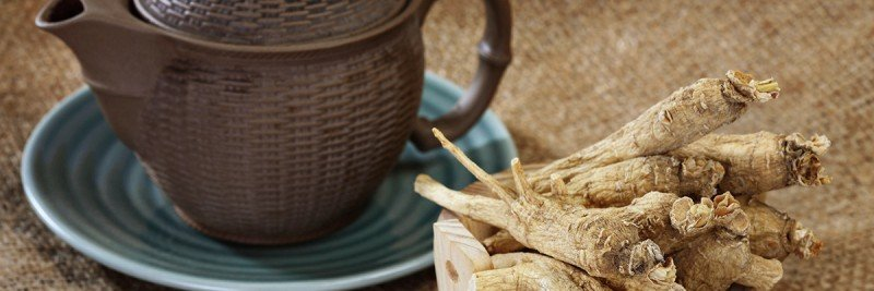 A bowl of ginseng root sitting next to a teapot.