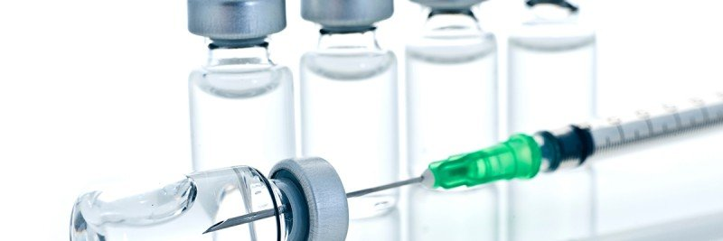 Needle entering a vaccine vial.