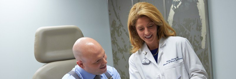 Female doctor on right in white coat conferring with male patient on the left.