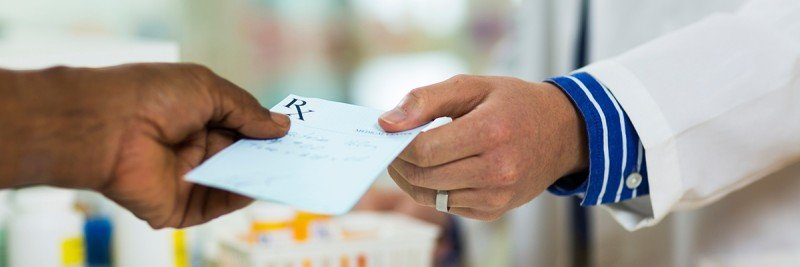 Patient hand giving prescription slip to pharmacist's hand.