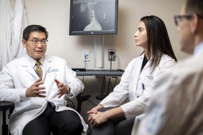 Radiation oncologist Josh Yamada and clinical nurse Cynthia Correa talking in an office.