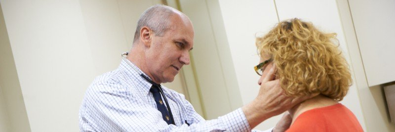 Doctor on left conducts examination of neck of patient who is on right.