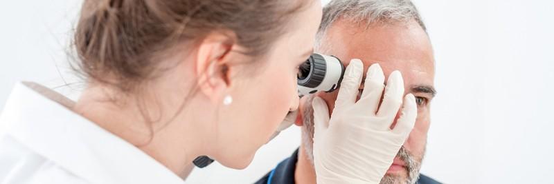 Dermatologist examining skin on the face of older man.