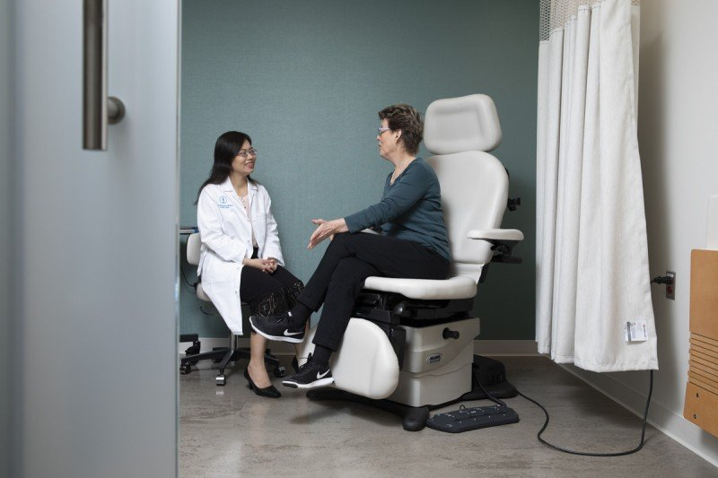 Breast medical oncologist Rui Wang (left) listens to a patient during an exam.