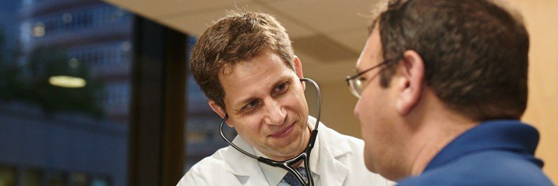 Medical oncologist Bill Tap examines a patient