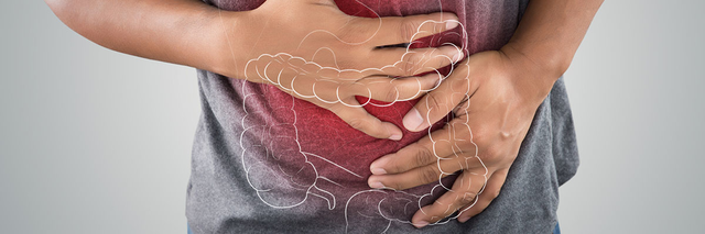 A man clutches his stomach in pain